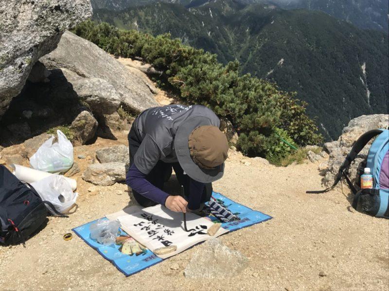 山頂で書道する女性